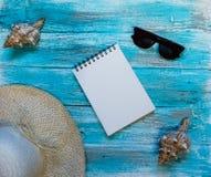 Heller Hintergrund mit blaue, blaue gemalt Farbenbretter, Sonnenbrille, Strohhut, ein offenes Notizbuch und Muscheln Beschneidung Lizenzfreie Stockfotos
