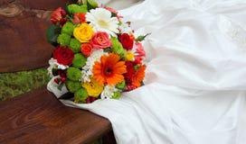 Heller Hochzeitsblumenstrauß auf weißem Kleid Lizenzfreies Stockfoto