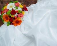 Heller Hochzeitsblumenstrauß auf weißem Kleid Stockbild