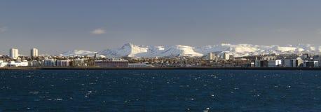 Heller Reykjavik gegen den Hintergrund von zasnezhenyh Bergspitzen stockfotografie