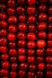 Heller roter Hintergrund von ordentlich gefalteten saftigen süßen Kirschen stockfotos