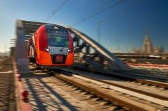 Heller roter Hochgeschwindigkeitspersonenzug verlässt den Tunnel Lizenzfreies Stockfoto