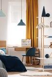 Heller Schlafzimmerinnenraum mit Einzelbett mit Türkisdecke auf weißer Bettwäsche und bunte Kissen und Spielzeug lizenzfreie stockfotografie