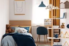 Heller Schlafzimmerinnenraum mit Einzelbett mit Türkisdecke auf weißer Bettwäsche und bunte Kissen und Spielzeug lizenzfreie stockbilder