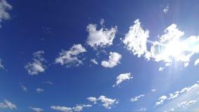 Heller Sonnenschein und Fliegen über dem blauen Himmel bewölkt sich stock footage