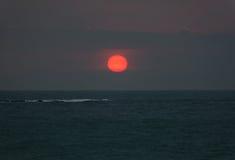 Heller Sonnenuntergang mit großer roter Sonne unter der Ozeanoberfläche Stockbild