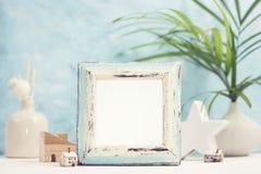 Heller tropischer Spott oben mit weißem und blauem Fotorahmen der Weinlese, Palmblättern im Vase und Hauptdekor gegen blaue Wand lizenzfreie stockfotografie