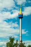 Heller Turm gegen den blauen Himmel mit Wolken Stockfotografie