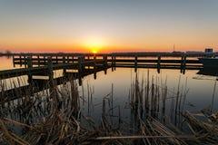 Heller und bunter Sonnenuntergang über einem See mit einem Pier entlang dem See 'Rottemeren 'in den Niederlanden lizenzfreie stockfotografie
