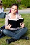 Heller weiblicher Kursteilnehmer, der ein Buch auf dem Gras liest Stockfotografie
