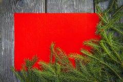 Heller Weihnachtshintergrund mit einem Kopienraum mit Tannenzweigen mit einem Holztisch und einer roten Beschaffenheit lizenzfreies stockbild