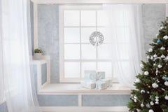 Heller Weihnachtsinnenraum mit Baum, Fenster und Geschenken Stockbild