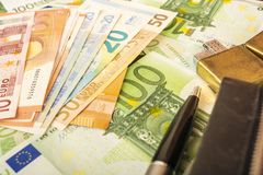 Hellerer Geldbeuteluhrstift auf dem Hintergrund von Euroanmerkungen des Geldes 100 Stockfotos