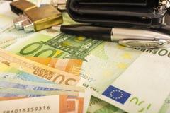 Hellerer Geldbeuteluhrstift auf dem Hintergrund von Euroanmerkungen des Geldes 100 Lizenzfreies Stockfoto