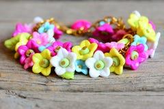 Helles Armband lokalisiert auf altem hölzernem Hintergrund Armband hergestellt von den bunten Plastikblumen, von den Blättern und Stockbilder