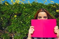 Helles Bildmädchen, das auf einer Bank auf einem grünen Blumenzaun sitzt Lizenzfreies Stockfoto