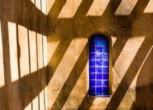 Helles blaues Fliesenfenster auf Gebäude des luftgetrockneten Ziegelsteines mit Schattenmuster Lizenzfreies Stockfoto