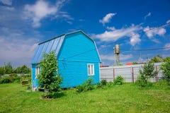 Helles blaues Sommerhaus, Zaun und elektrische Drähte auf einem Hintergrund des blauen Himmels mit weißen Wolken Stockfotografie