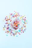 Helles farbiges Süßigkeitenbesprühen von Sternen in einem Glasgefäß auf einem hellen Hintergrund Weichzeichnung, Unschärfe Stockfoto