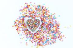 Helles farbiges Süßigkeitenbesprühen von Sternen und von hölzernem Herzen auf einem hellen Hintergrund, Weichzeichnung, Unschärfe Lizenzfreies Stockfoto