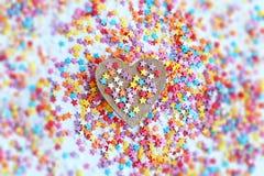 Helles farbiges Süßigkeitenbesprühen von Sternen und von hölzernem Herzen auf einem hellen Hintergrund, Weichzeichnung, Unschärfe Lizenzfreies Stockbild