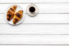 Helles Frühstück kleine Schale des schwarzen Kaffees und des Hörnchens auf weißem hölzernem copyspace Draufsicht des Hintergrunde stockfotos
