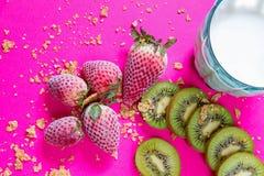 Helles Frühstücksbild - Getreide, blaues Glas Kuhmilch und Früchte am pinkfarbenen Tisch stockfoto