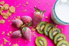 Helles Frühstücksbild - Getreide und Früchte am pinkfarbenen Tisch stockfoto