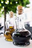 Helles gelbes Olivenöl und schwarzer Balsamico-Essig auf dem Restaurantküchentisch Vordergrund mit zwei Flaschen Abfüllen von lizenzfreies stockfoto