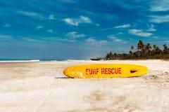 Helles gelbes Surfbrett in Form eines Zeigers mit einer roten Wortrettung auf einem sandigen Strand am Nachmittag Rettungsschwimm lizenzfreie stockfotografie