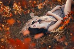 Helles Herbstkunstfoto, Göttinreste im orange Wald des Herbstes unter Schutz des netten Steinkauzes, Mädchen mit dem dunklen Haar lizenzfreie stockfotos