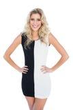 Helles lächelndes blondes Modell, das Hände auf Hüften aufwirft Lizenzfreies Stockfoto