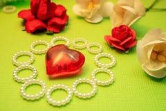 Helles Liebesthema für Grüße, Herzen und Blumen auf einem grünen Hintergrund Stockfotografie