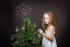 Helles Mädchen steht nahe dem Weihnachtsbaumkonzept Lizenzfreie Stockfotografie