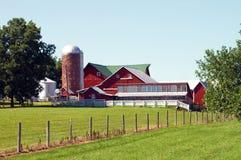 Helles rotes Bauernhaus und Silo im Mittelwesten Lizenzfreie Stockfotografie