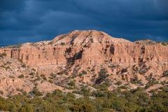 Helles Sonnenlicht belichtet eine bunte rote Hammadaspitze und -ödländer unter den dunklen, drastischen Sturmwolken nahe Santa Fe stockbild