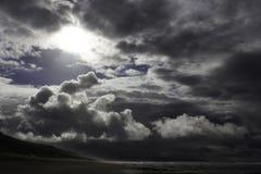 Helles Sonnenlicht, das durch eine Reinigung in einem stürmischen Küstenhimmel glänzt lizenzfreies stockbild