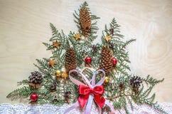 Helles Sperrholz mit einem Weihnachtsbaum, gemacht von Zweige Thuja mit Tannenzapfen Stockfotografie