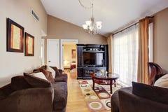 Helles Wohnzimmer mit braunem Sofa und bunter Wolldecke Stockbild