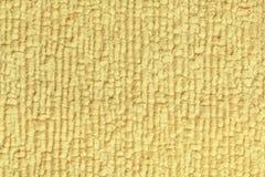 Hellgelber flaumiger Hintergrund des weichen, wolligen Stoffes Beschaffenheit der Textilnahaufnahme Lizenzfreie Stockfotos