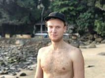 Hellhäutiger blonder Kerl in einer Kappe auf dem Strand ohne bräunen sich ohne Oberbekleidungslächeln lizenzfreies stockfoto