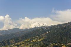 Helling met groene bos, gebieden en huizen tegen de achtergrond van de sneeuwberg van Annapurna met witte wolken en blauw stock afbeeldingen