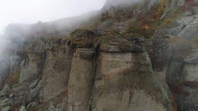 Helling van berg in mistschot De dichte grijze mist wikkelt volledige ruimte Hoogste mening van rots die zich in koude de herfstm stock afbeelding