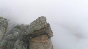 Helling van berg in mistschot De dichte grijze mist wikkelt volledige ruimte Hoogste mening van rots die zich in koude de herfstm royalty-vrije stock foto