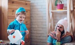 Hello är jag din doktor Sonen med första hjälpenasken tar omsorg av fadern hemma Doktor för lek för litet barn med mannen Pojke i Royaltyfria Foton