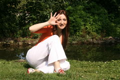 Hello. A young woman waving hello as she sits next to a pond Stock Photo