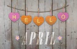 Hello April bij het hangen van roze en oranje harten en doorstane houten achtergrond wordt geschreven die stock afbeelding
