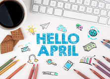 Hello april, Business concept. Computer keyboard and cup of coffee on a white table Stock Image