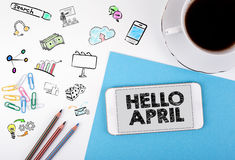 Hello april, business Concept. Mobile phone and coffee cup on a white office desk Stock Photo