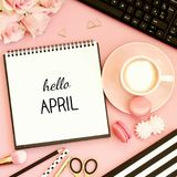 Hello April text on notebook. Office table with notebook, cup of coffee, sweet snacks, pen, pencil and flowers. Pink pastel, black and white, golden tones. Top Royalty Free Stock Photography